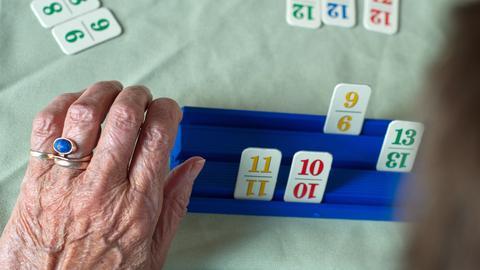 Ein Tisch mit Rummikub-Spielsteinen und der Hand einer älteren Frau