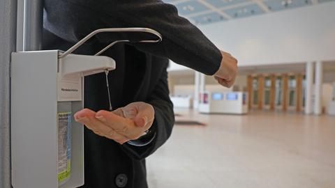 Ein Mann desinfiziert seine Hände und drückt dabei vorschriftsmäßig den Bügel des Spenders mit seinem Ellenbogen herunter.