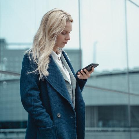 Eine hippe junge Frau, die auf ihr Smartphone guckt