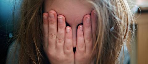 Mädchen hält sich Hände vor das Gesicht