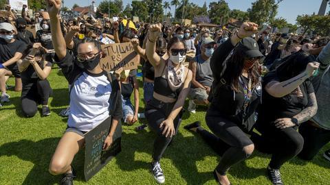 Demonstranten strecken ihre Fäuste in die Höhe und knien schweigend nieder im Village Green Park.