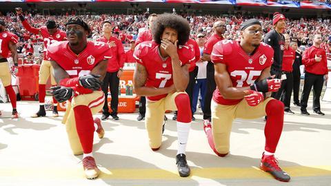 Colin Kaepernick (M), Eli Harold (L) und Eric Reid (R) von den San Francisco 49ers knien bei der US-Nationalhymne.