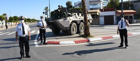 Polizeibeamte und Soldaten mit Mundschutz wachen auf einer Straße in Salé, Nachbarstadt von Rabat.
