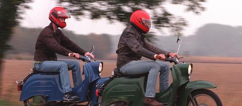 """Zwei junge Männer fahren mit ihren """"Schwalbe""""-Rollern über einen Feldweg."""