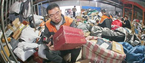 Arbeiter sortieren Unmengen von Paketen bei einem Logistikunternehmen