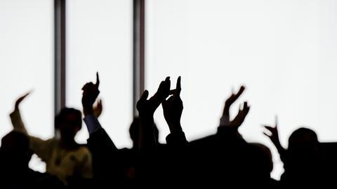 Hände, die zur Abstimmung in die Höhe gehalten werden