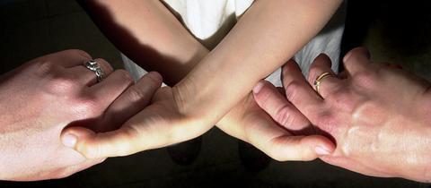 Kleinkind hält zwei erwachsene Hände