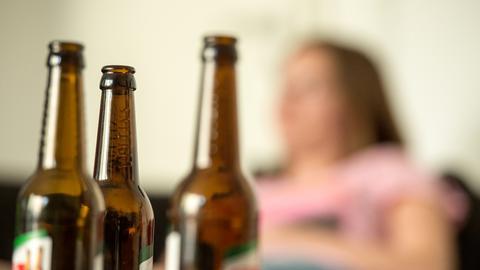 Frau sitzt hinter drei Flaschen Bier