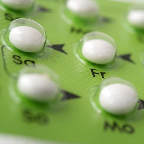 Weiße Pillen in durchsichtiger Verpackung mit grünem Grund
