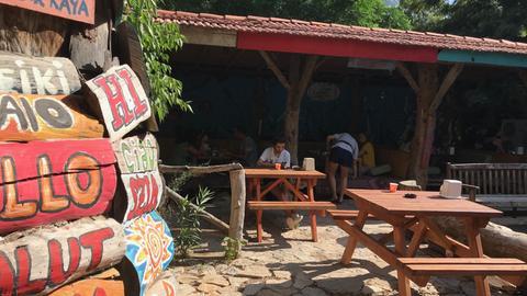 Vor der Restaurant-Terrasse werden Gäste auf Schildern in verschiedenen Sprachen begrüßt.