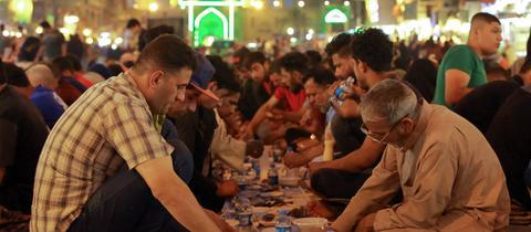 Muslime haben sich unter freiem Himmel zu einem kostenlosen öffentlichen Abendmahl (Iftar) während des muslimischen Fastenmonats Ramadan im Stadtteil Kadhimiya (Badgad) versammelt