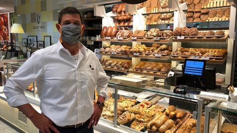 Bäckermeister Dries mit Mundschutz vor seiner Ladentheke