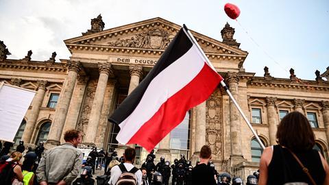 Bei den Protesten gegen die Corona-Maßnahmen in Berlin trägt ein Teilnehmer eine Reichsflagge