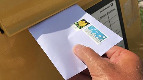 Ein Brief wird in einen Briefkasten geworfen