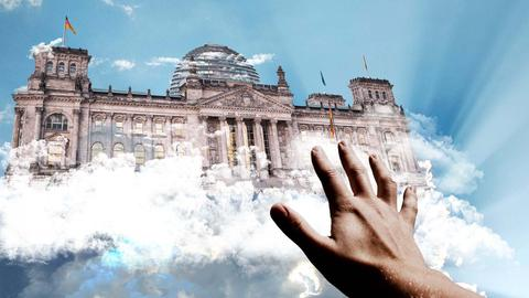 Eine Hand greift nach dem Bundestag