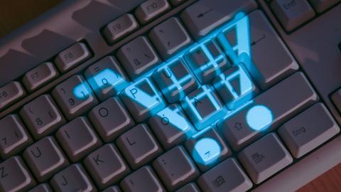 Symbol eines Einkaufswagens leuchtet auf einer Computertastatur