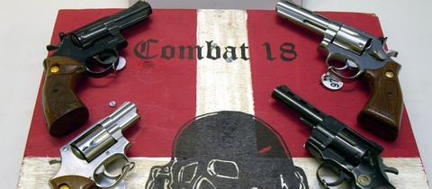 Sichergestellte Waffen und ein Schild der Neonazi-Gruppe Combat 18