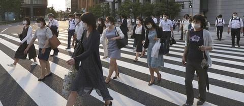 Menschen tragen beim Überqueren einer Kreuzung in Tokio Mundschutze.