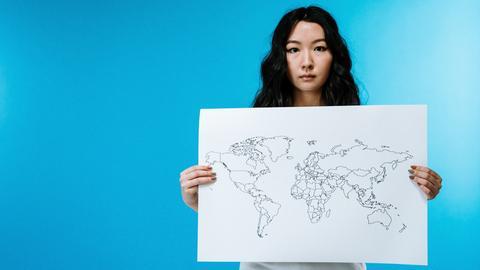 Frau hält eine Weltkarte