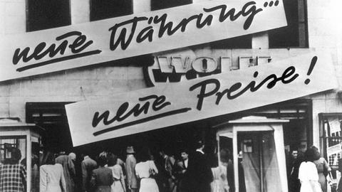 """Kundenandrang vor einem Geschäft, das nach der Währungsreform Schilder mit der Aufschrift """"Neue Währung... neue Preise!"""" an der Hausfassade angebracht hat."""