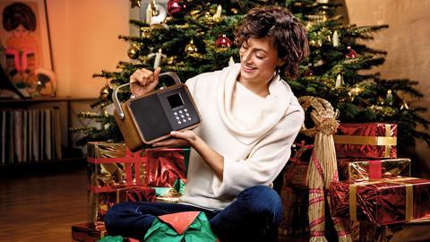Eine Frau freut sich über ein DAB+-Radio unterm Weihnachtsbaum