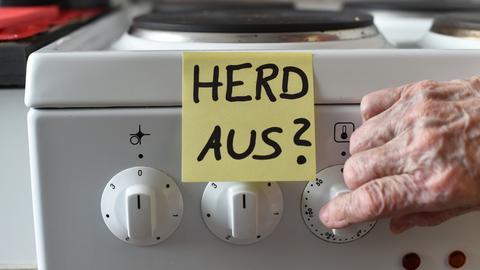 """Ein Klebezettel mit dem Schriftzug """"Herd aus?"""" klebt an einem Herd neben den Drehknöpfen."""