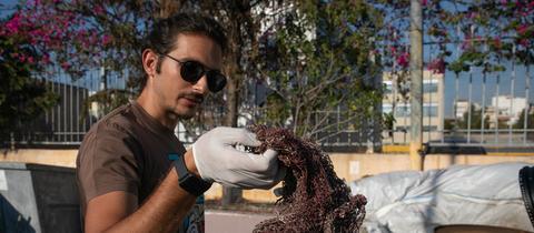 Lefteris Arapakis hält ein Fischernetz aus Plastik hoch.