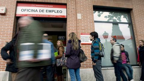 Arbeitslose stehen in einer Schlange vor einem Arbeitsamt.