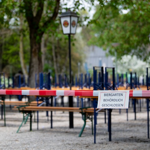 """Ein verwaister Biergarten in München. Auf einem Schild steht: """"Biergarten behördlich geschlossen"""""""