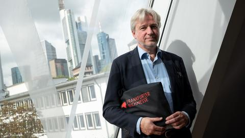 der Direktor der Buchmesse Jürgen Boos auf dem Frankfurter Messegelände mit der Skyline im Hintergrund