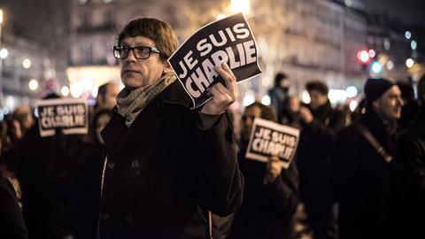 """Nach dem Anschlag auf Charlie Hebdo halten Menschen in Paris """"Je suis Charlie""""-Plakate in die Höhe."""