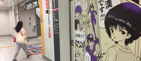 """Ein Plakat auf einem Bahnhof in Yokohama, auf dem erklärt wird, dass """"chikan"""", Grabschen ein Verbrechen ist."""