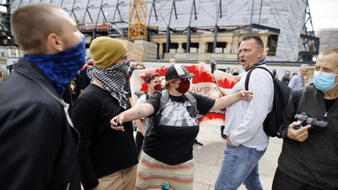 Teilnehmer einer Demonstration gegen die Anti-Corona-Maßnahmen werden von Gegendemonstranten getrennt.