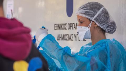 Mitarbeiterin der Nationalen Griechischen Gesundheitsorganisation EODY mit Teststäbchen beim Abstrich für einen Antigen Schnelltest.
