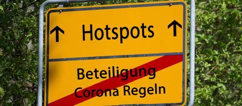 """Auf einem Ortsschild sind """"Hotspots"""" ausgeschildert. Durchgestrichen ist untendrunter """"Beteiligung Corona Regeln"""""""