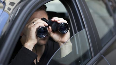 Ein Mann sitzt im Auto und beobachtet etwas mit einem Fernglas.