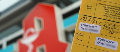 Ein Impfpass weist zwei Corona-Impfungen auf. Im Hintergrund ist ein Apothekenschild zu sehen.