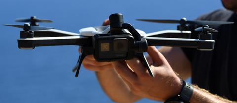 Ein Mann hält eine Drohne in der Hand