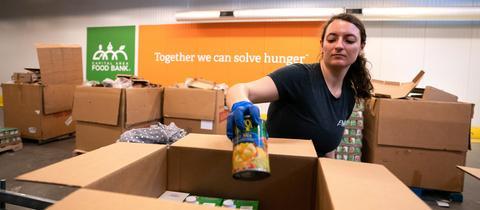 Eine Freiwillige packt Lebensmittel für Bedürftige in eine Kiste