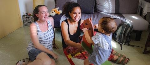 Ein Kind sitzt auf einem Schaukelpferd im Wohnzimmer, seine beiden Mütter sitzen daneben.