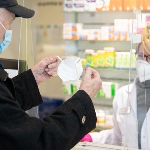 Eine Apothekerin überreicht einem älteren Kunden eine FFP2-Maske