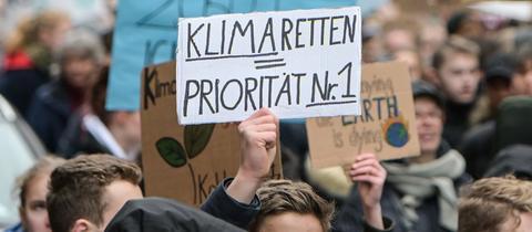 """Auf einer Klimaschutz-Demo hält ein Junge ein Plakat hoch: """"Klima retten - Priorität Nr. 1"""""""