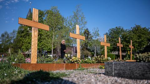 Auf einem Friedhof reihen sich Holzkreuze dicht an dicht