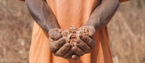 Sujetbild: Ein schwarzer Mann hält mit Gold zersetze Erde in seinen Händen.