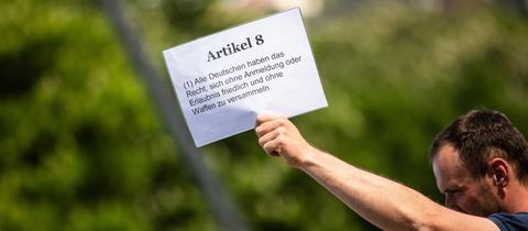Ein Demonstrationsteilnehmer macht mit einem Schild auf die Einschränkung der Grunderechte aufmerksam.