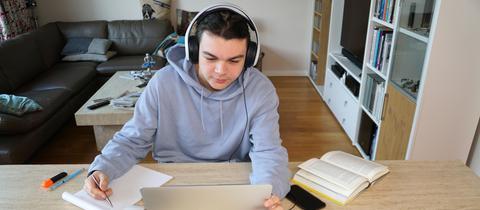 """Sujetbild: Ein Jugendlicher sitzt Zuhause am Schreibtisch und """"besucht"""" die Schule per Laptop."""