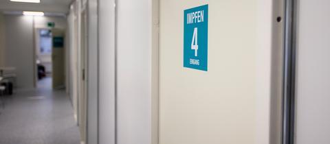 """Auf einer Tür in einem Impfzentrum in Schweinfurt steht groß """"Impfen"""""""