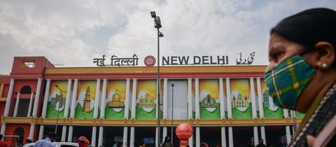 Eine Frau vor dem Bahnhof Neu-Delhi