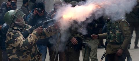 Ein indischer paramilitärischer Soldat feuert bei einem Protest in Kaschmir eine Tränengasgranate ab.