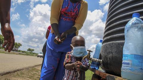 Eine Familie in Kenya wäscht sich die Hände an einer Bushaltestelle